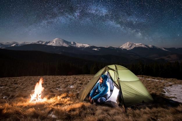 Женский турист, наслаждаясь в своем лагере ночью под красивым небом, полным звезд и млечного пути