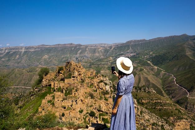 Туристка высоко в горах дагестана любуется захватывающим панорамным видом на природу и древний заброшенный город гамсутль. делает фотографии достопримечательностей и руин, селфи на смартфон.