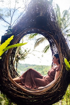 A female tourist is sitting on a large bird nest on a tree at ba