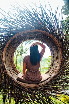 A female tourist is sitting on a large bird nest on a tree at bali island