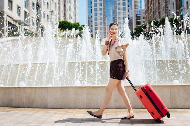 女性観光客。ホテルを探している間彼女のスーツケースを運ぶうれしそうな幸せな女