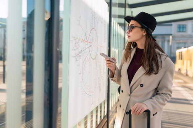 Female tourist looking the routes map at the bus stop.