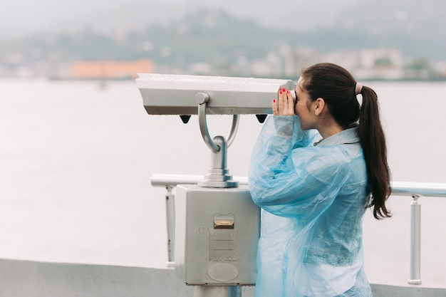 Female tourist looking through coin operated binoculars with sea view in rainy weather