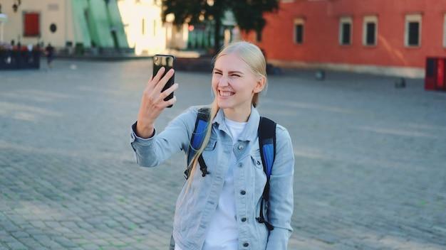 Туристка делает видеозвонок на смартфон с места своего визита. достопримечательности красивого европейского города.