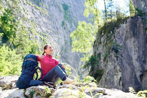 Женский турист отдыхает на скале, любуясь красотой захватывающих скалистых гор