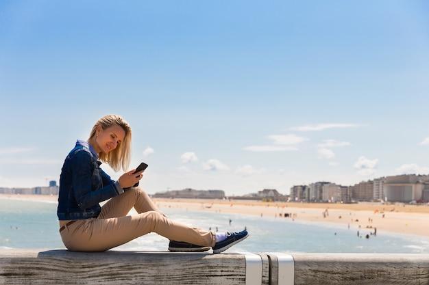 Туристка, сидящая на пирсе на городском пляже, морское побережье, европа. летний туризм и путешествия, известные и популярные места для отпуска или отпуска