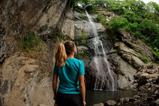 Female tourist in sportswear standing near waterfall