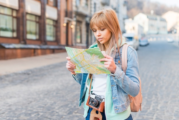 Female tourist standing on city street looking at map