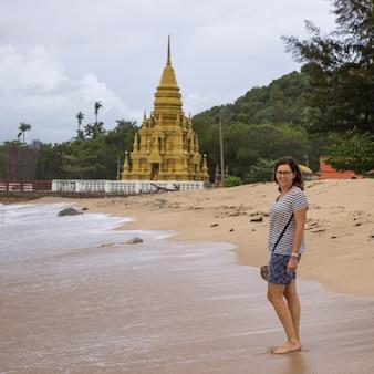 Женский турист, стоящий на пляже с пагода лаем-сор на заднем плане, кох-самуи, сурат-тани Premium Фотографии