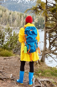 Female tourist stands back to camera, dressed in casual yellow raincoat, rubber boots, breathes fresh air near mountain lake, leads active lifestyle
