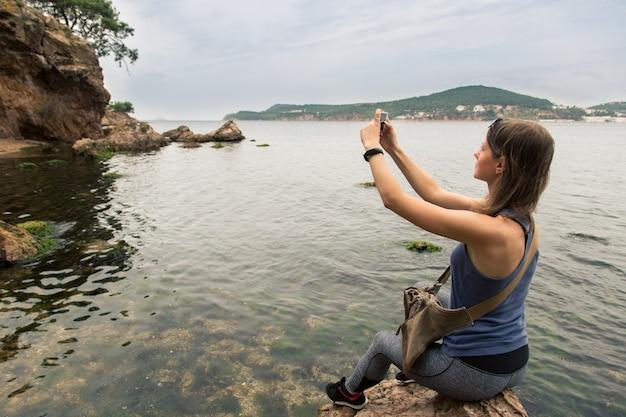여성 관광객은 지중해로 바위에 앉아 휴대 전화로 사진을 찍습니다.