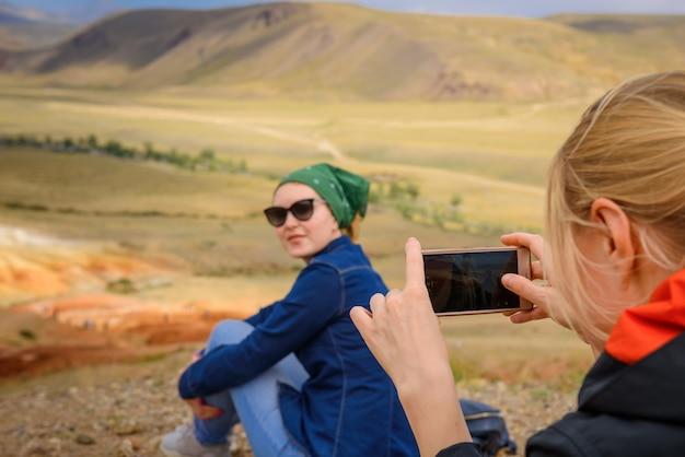 女性観光客は、スマートフォンで彼女のガールフレンドの写真を美しい見晴らしの良い場所で、クローズアップして、選択的に焦点を合わせて撮影します。
