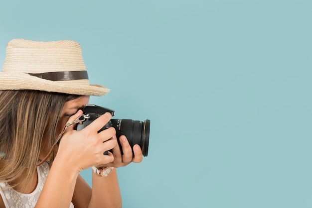 Female tourist takes a picture with professional camera against blue backdrop