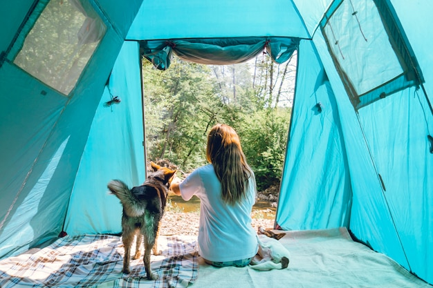 Female tourist traveler in camp in a forest with her dogs together on a nature trip, friendship concept, outdoor activities, traveling with a pet.