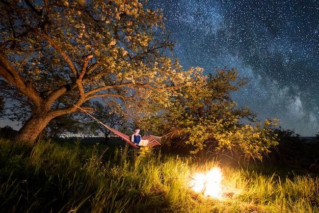 밤에 캠핑에서 그녀의 노트북을 사용 하여 여성 관광. 나무와 별과 은하수가 가득한 아름다운 밤하늘에서 모닥불 근처 해먹에 앉아있는 여자