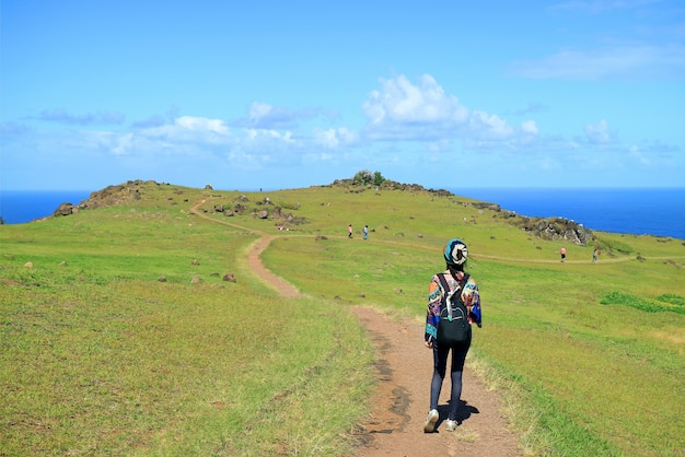 Female tourist visiting orongo village, the historic ceremonial center on easter island, chile