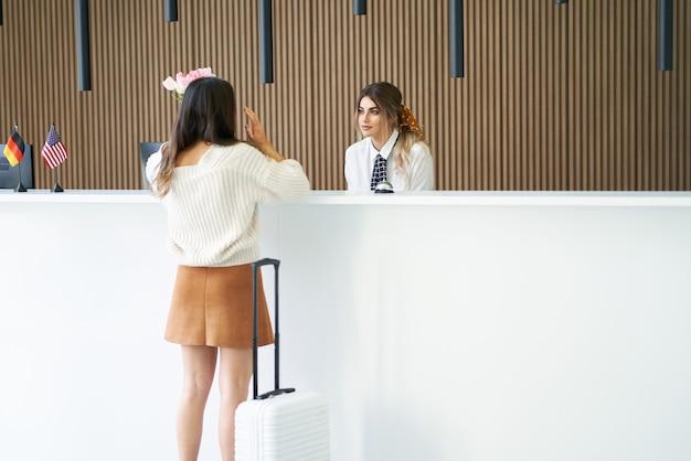 Туристка ждет на стойке регистрации в отеле