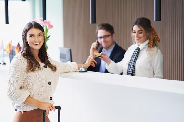 ホテルの受付で待っている女性観光客