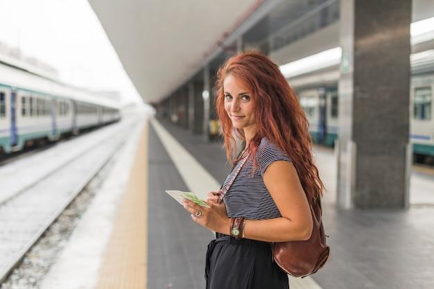 Женский турист ждет поезд