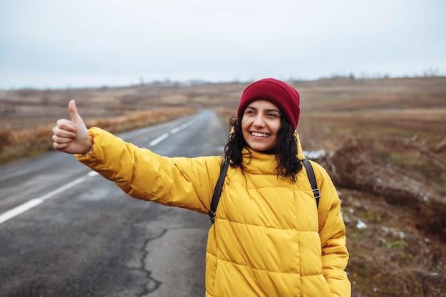 노란색 재킷과 빨간 모자를 쓰고 배낭을 든 여성 관광객은 도로에서 차를 잡는다.