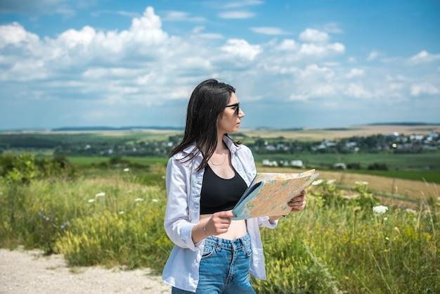 晴れた夏の日に道路を歩いている地図を持つ女性観光客。休暇の概念