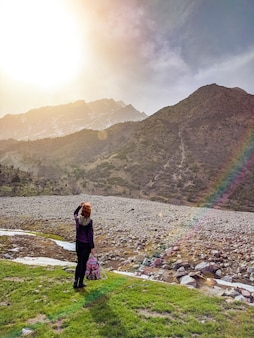 Female tourist with a backpack, admiring the mountains, walking in the mountains in the su