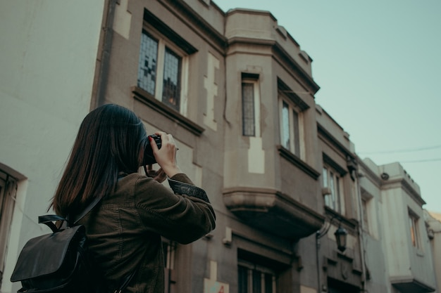 Female tourist with a backpack photographing a building