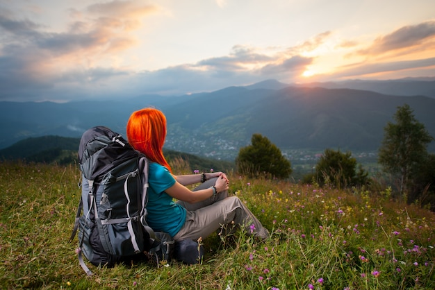 Female tourist with backpack sitting in the grass at sunset