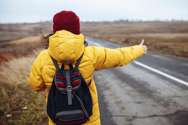 Female tourist with a backpack wearing yellow jacket and red hat catches a car on the road.