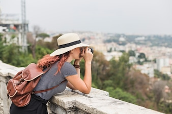 Female tourist with camera on balcony