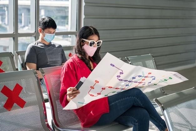 얼굴 마스크를 쓴 여성 관광객은 공항 터미널 대기 석에서 지하철을 읽으며 여행을 계획합니다.