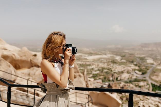 短い髪型の女性観光客が日光の下で街を眺めながら古い岩の間で写真を撮っています
