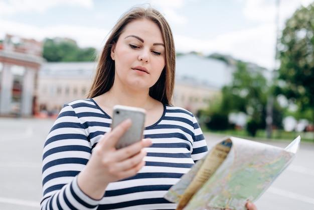 屋外の方向を探している手でスマートフォンと紙の地図と女性観光客