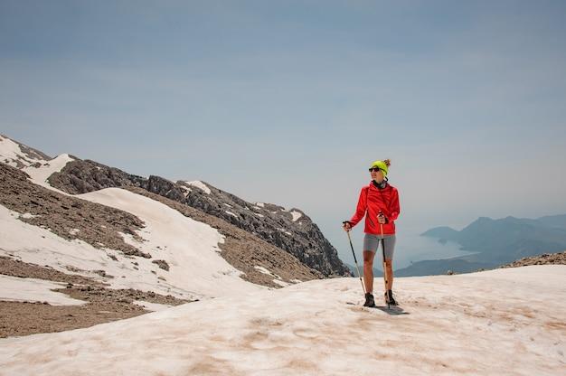 山で杖を持つ女性観光客