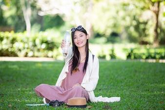 女性観光客は水を飲んでいます。