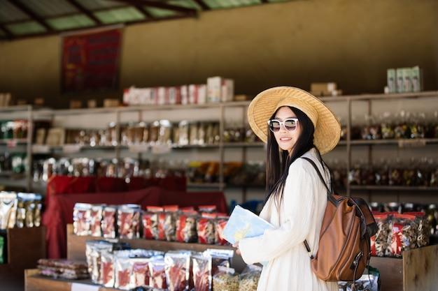 여성 관광객이 쇼핑을 걷고있다.