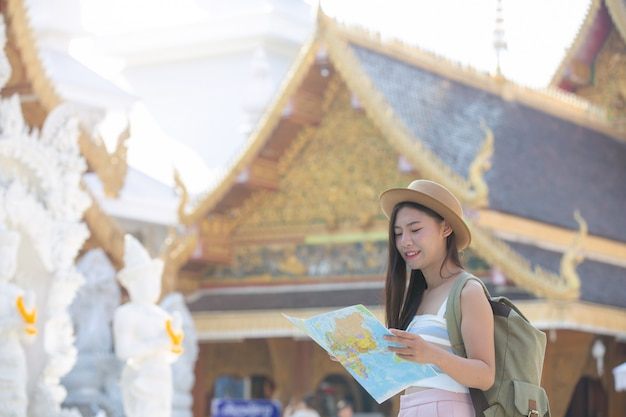 Female tourists hold a map to find places.