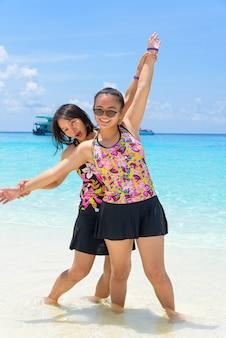 Женщина-туристка, мать и дочь в купальниках, счастливо улыбаются на пляже на острове ко мианг - прекрасные морские достопримечательности в национальном парке му ко симилан, провинция пханг нга, таиланд.
