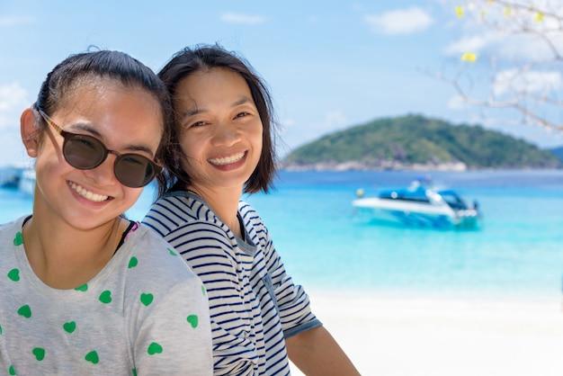 Женщина-туристка, мать и дочь, счастливо улыбаются на пляже на острове кох мианг - красивые достопримечательности и известные моря в национальном парке му ко симилан, провинция панг нга, таиланд.