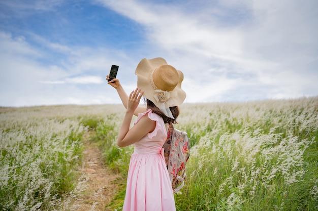 彼女が牧草地で自撮り写真を撮っている女性観光客。
