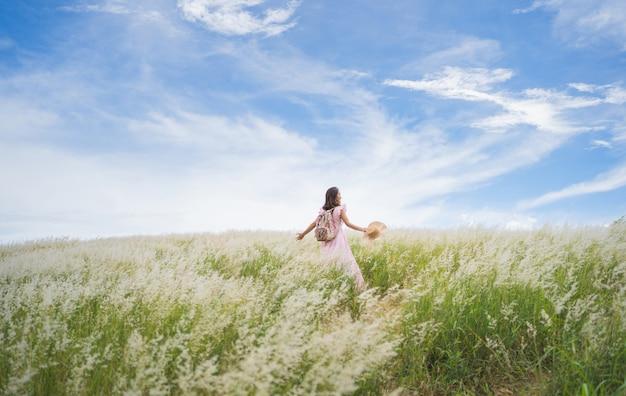 女性観光客彼女は牧草地を旅行しています。