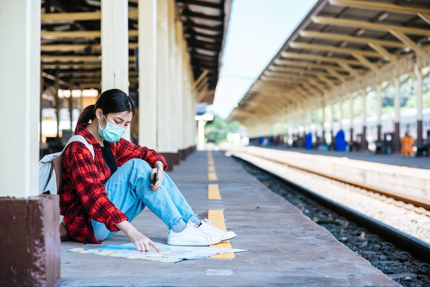 Female tourists sit and look at the map on the footpath beside the railroad.