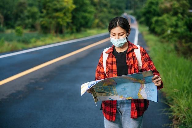 Женщины-туристы стоят и смотрят на карту на дороге.