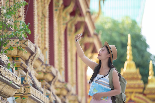 Female tourists take pictures with mobile phones