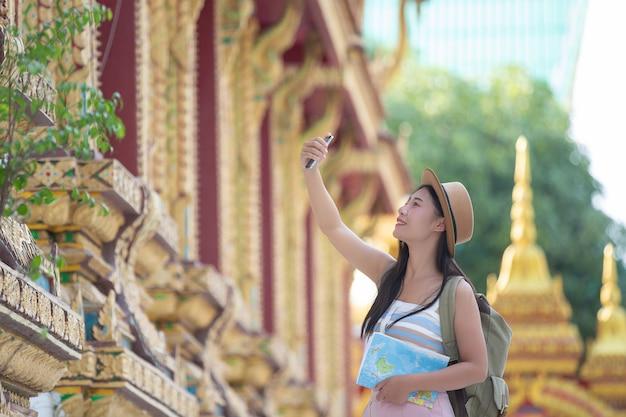 여성 관광객은 휴대 전화로 사진을 찍습니다
