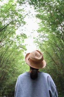 トンネルの竹の木と歩道の背景を見ている女性観光客。