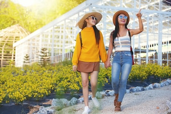 Female tourists walk holding arms