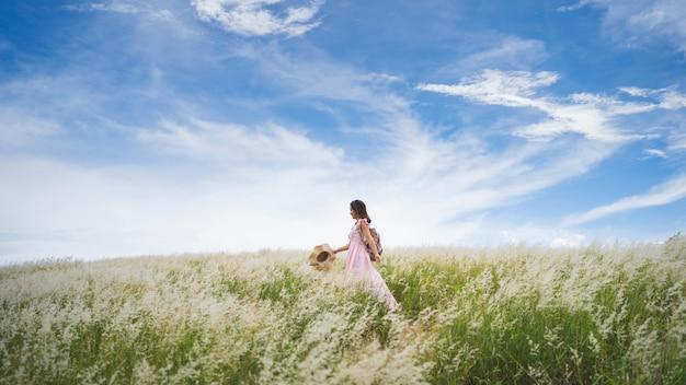晴れた日に牧草地を歩く女性観光客
