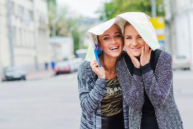 Женщины-туристы с картой на голове Бесплатные Фотографии