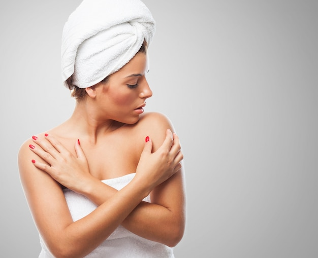 Female in towel touching her shoulders.